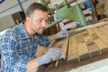 Carpenter aligning planks of wood