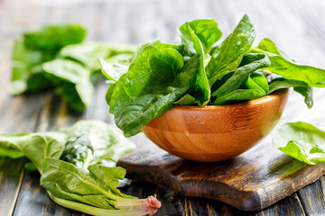Wooden bowl with fresh spinach leaves.