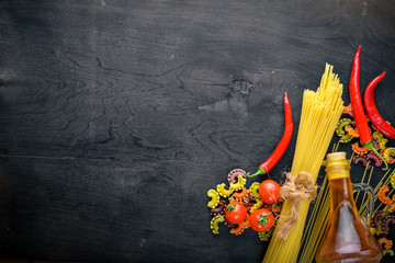 Pasta with vegetables, cherry tomatoes, chili peppers and garlic. On a wooden background. Free space for text . Top view.