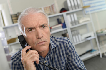 Man on telephone, looking pensive
