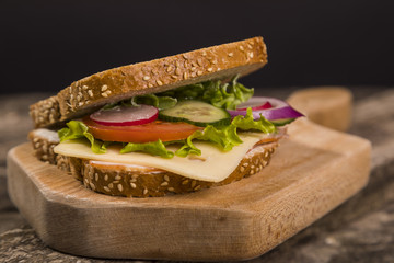Healthy sandwich made with whole grain bread, lettuce, tomato, radish, cheese and roasted chicken slices.