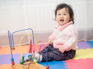 cute smiling baby girl play toy at home