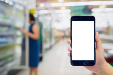 Woman hold mobile phone while shopping in supermarket