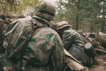 Re-enactors Dressed As German Wehrmacht Infantry Soldiers In World War II Hidden Sitting