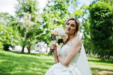 Cute blonde bride with wedding bouquet at park on sunny day.