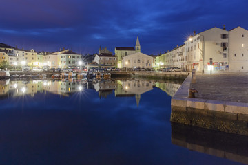 Europe, Slovenia, Primorska, Izola. Old town and the harbour with fishing boats at night