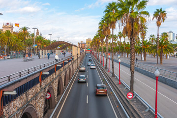 Late afternoon in Seaside Barcelona, Spain, sees traffic in tunnelled streets & pedestrian traffic above as people enjoy walking outdoors along the waterfront in warm November weather.