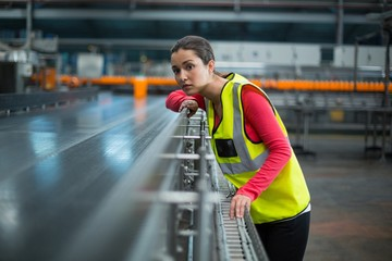 Female factory worker checking conveyor belt