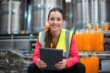 Female factory worker holding digital tablet