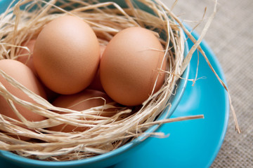 Brown chicken eggs on a blue plate