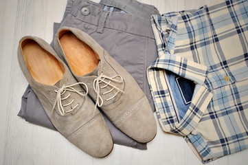 Beige pants, plaid shirt and gray suede shoes. Overhead view of men's casual outfits on white wooden background.