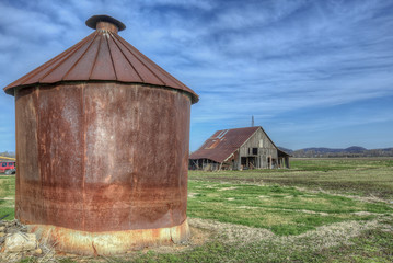 Old rusty metal silo and derelict barn along Rt. 79 just North of Annada Missouri.
