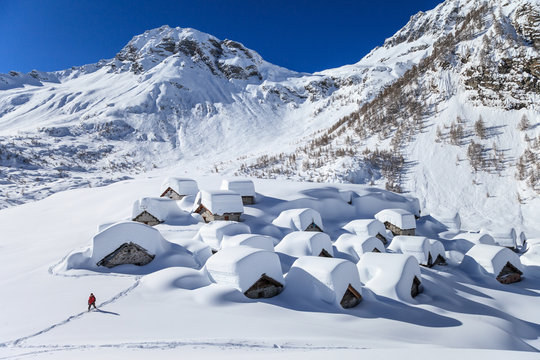 View of snow covered houses against mountain during winter