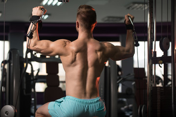 Muscular Man Exercising Shoulders On Machine