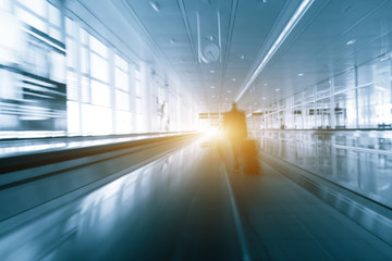 Abstract motion blured silhouette of a unrecognizable business travelers people at international airport moving to terminal gate for airplane travel trip