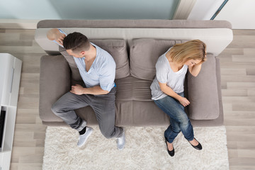 Upset Couple Sitting On Couch