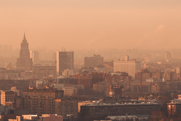 Close-up shooting from high point of metropolitan city: residential buildings and districts illuminated by morning sun, tower, multiple facades and windows, Government building, hazy horizon, Moscow