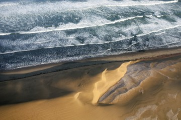 Aerial view of the sand dunes meeting the ocean. Namibia, South Africa