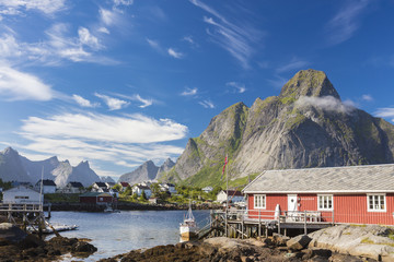 Typical house of fishermen called Rorbu framed by rocky peaks and blue sea Reine Moskenes Lofoten Islands Norway Europe