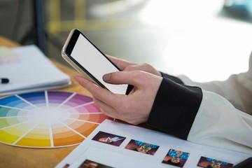 Female graphic designer using mobile phone at desk