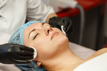 The cosmetician washes and cleanses the client's face before the cosmetic procedure. Preparation for peeling.