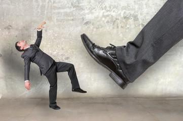 Businessman big foot kicking small businessman