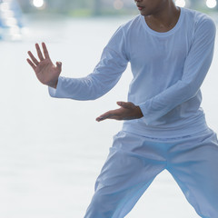 oung man practicing Tai Chi or Tai qi in the morning at the park for healthy, Tai Chi concept.