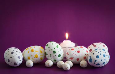 Speckled eggs big ones and little ones with lit candle on purple background