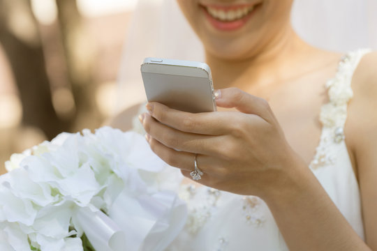 Asian bride smile and talking with her friend in smartphone in wedding day