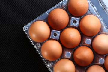 The chicken egg put on the plastic containing  tray represent the food packaging and food concept related idea.