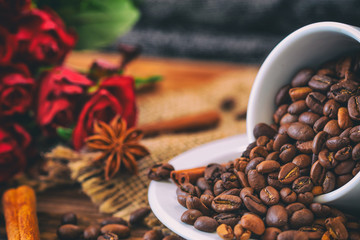 Cup filled with coffee beans on old wooden table with roses in the background.