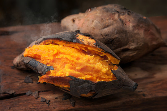 Delicious baked sweet potato on wooden table