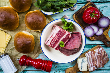 Ingredients for a burger with beef with spinach on a wooden background.