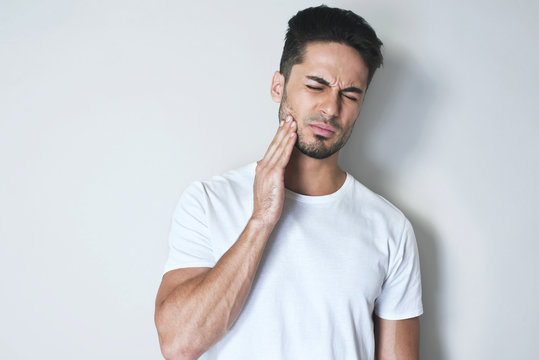 Portrait young man touch cheek. He has strong toothache and suffering from pain wearing casual white t-shirt against grey background. Feel toothache