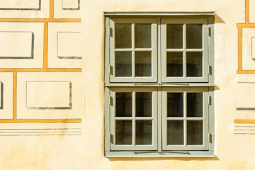 Architectural detail of green wooden window on yellow stone wall with part of painted pattern visible.
