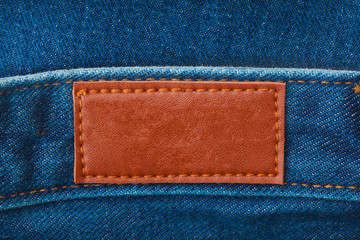 close up of blank leather label on blue denim for graphic design or branding