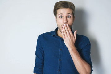 Young attractive man in blue shirt amazed in shock covering his mouth with hand and looking at camera against grey background. The sign of silence