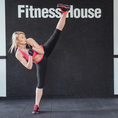 boxer woman giving kick in the gym on black white background
