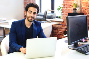 Arab businessman in jacket sitting on workplace with the notebook
