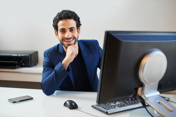 An Arab  businessman in a jacket sitting on workplace behind computer in office