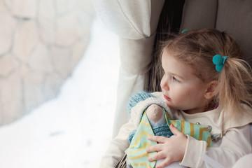 pretty little girl standing by window