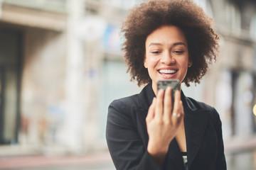Smiling businesswoman taking a selfie on a street