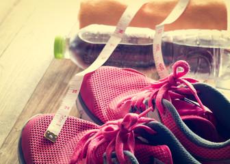 Sneakers, towel, water and tape measure on wooden floor