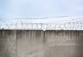 Concrete wall, against the backdrop of barbed wire, the concept of prison, salvation, Refugee, lonely, space for text, free