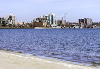 Urban area skyline with cranes seen across a deep blue lake, beach in foreground, sky