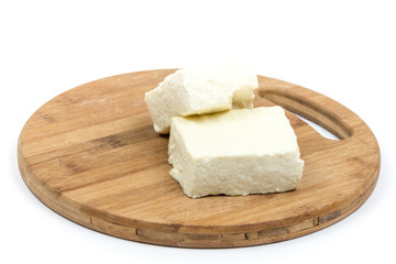 White feta cheese slices on the wooden board