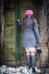 Girl in a pink beret and a gray-blue coat knocking on the door of the old house/The picture was taken in Russia, in the city of Orenburg, in Malo-Torgovy Lane.