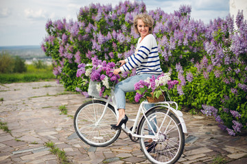 Adult woman in a striped sweater and jeans near a retro bike with flowers