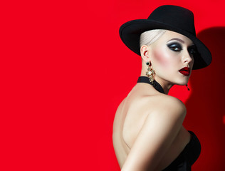 Beautiful fashionable girl with blonde hair rock in a black hat with red lips, eyes smokeys. Girl in the studio on a red background,  photoshoot. Advertising cosmetics.