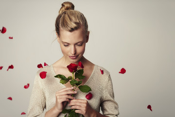 Beautiful woman with red rose petals, studio